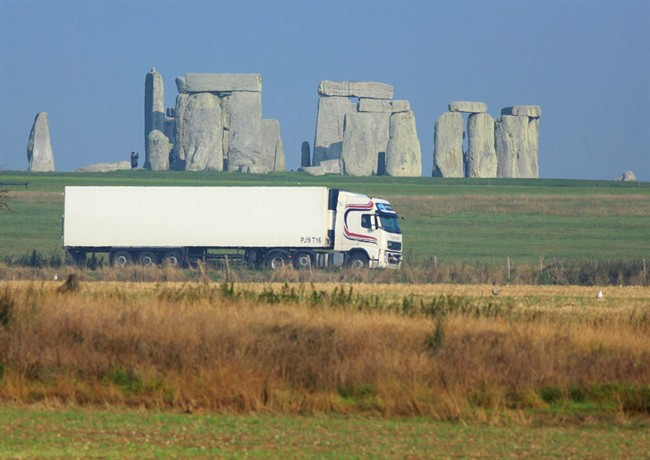 This is an undated handout photo issued by the National Trust, via the Press Associated of a truck passing Stonehenge on the A303 road in Wiltshire England. (AP Photo/John Miller/National Trust/PA).