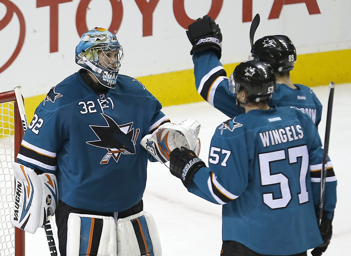 San Jose Sharks goalie Alex Stalock (32) is congratulated by teammates Barclay Goodrow (89) and Tommy Wingels (57) after a 5-2 victory against the Edmonton Oilers in an NHL hockey game Tuesday, Dec. 9, 2014, in San Jose, Calif.