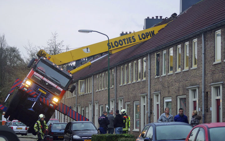 A crane which crashed into the roof of a house is seen following an unusual marriage proposal by a man who wished to be lifted in front of the bedroom window of his girlfriend to ask for her hand in marriage, in the central Dutch town of IJsselstein, Saturday Dec. 13, 2014.