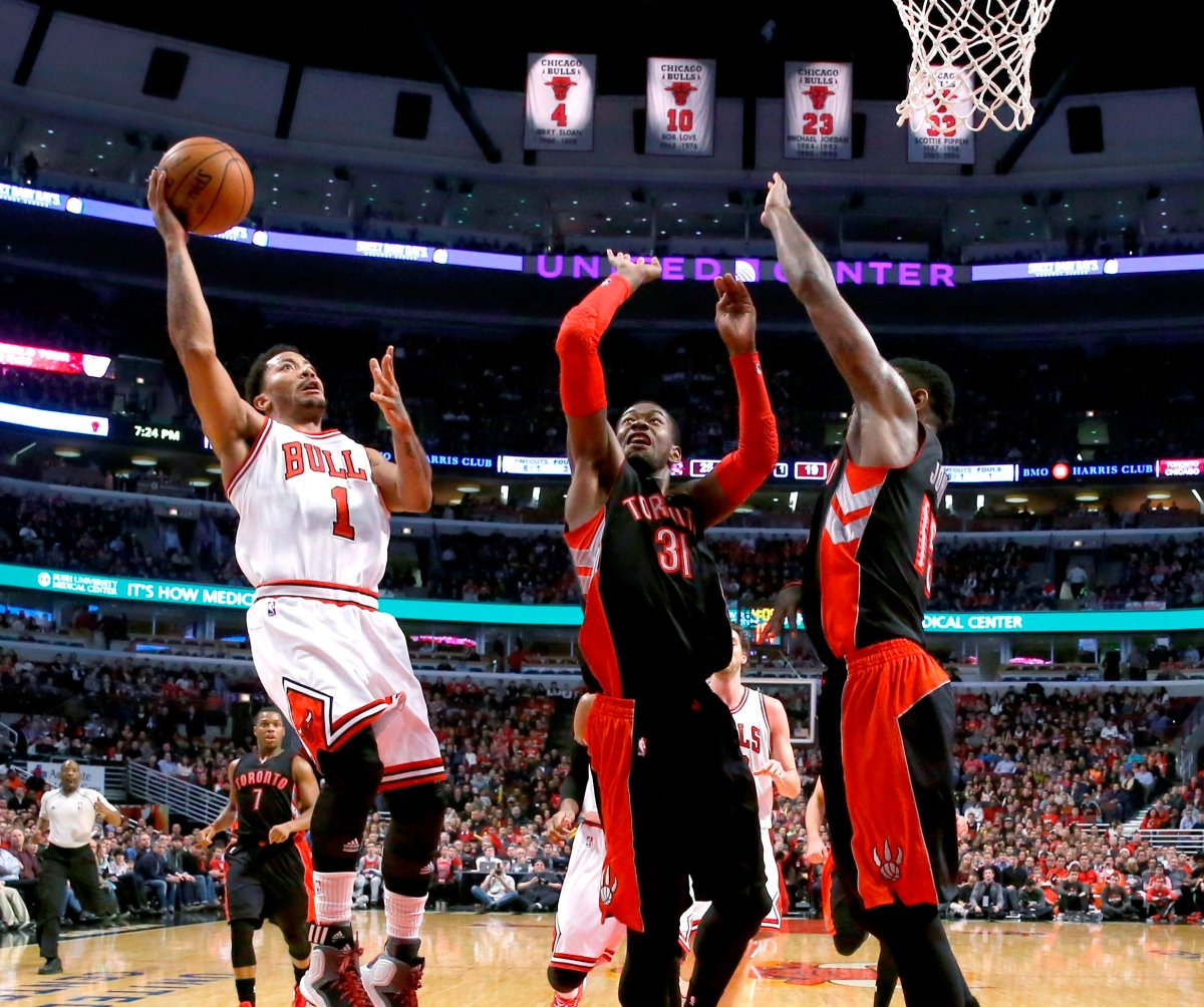 Chicago Bulls guard Derrick Rose (1) shoots as Toronto Raptors' Terrence Ross (31) and Amir Johnson (15) defend during the first half of an NBA basketball game Monday, Dec. 22, 2014, in Chicago.