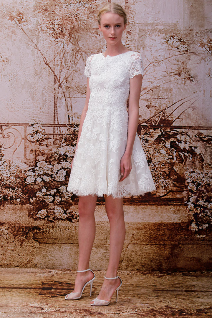 """This 2013 image released by the Monique Lhuillier fashion house shows the Opal, a silk white re-embroidered lace short-sleeved mini-wedding dress. """"A lot of people are doing more intimate settings, so a shorter dress just feels more appropriate. If they do the big wedding, some change into a shorter dress so they can dance and have a good time,"""" designer Monique Lhuillier said."""