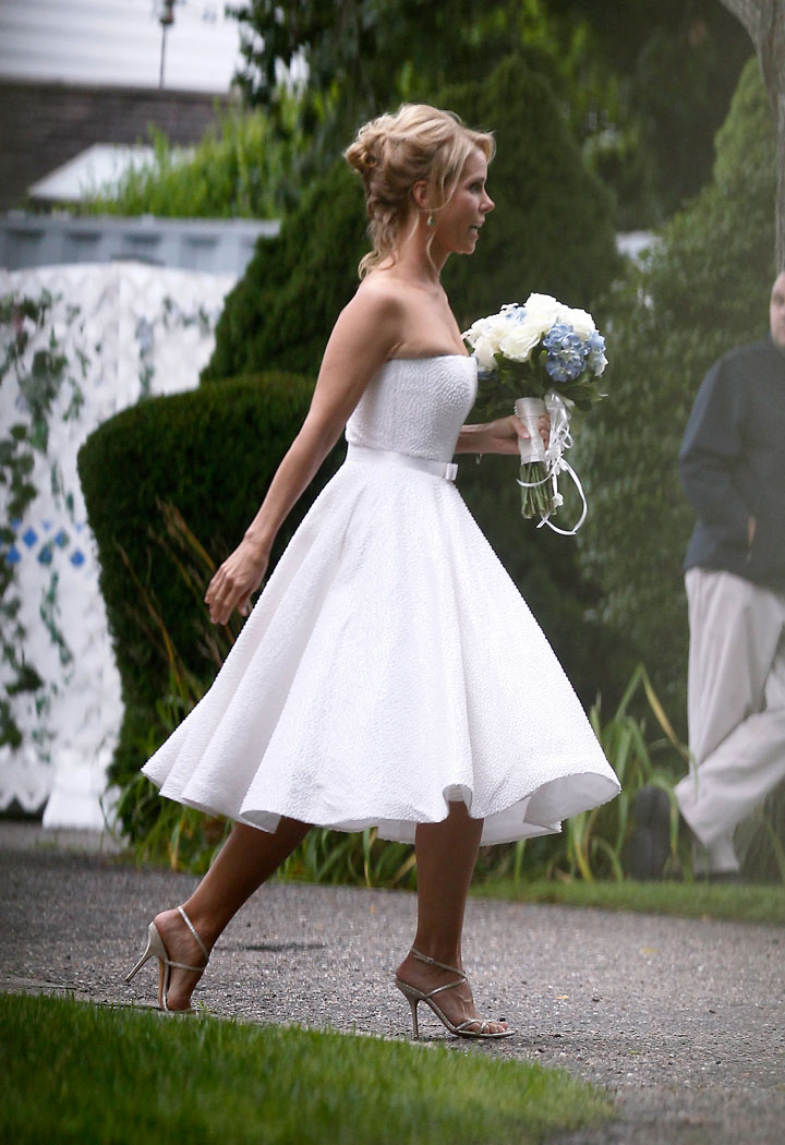 In this Aug. 2, 2014 file photo, actress Cheryl Hines wears a Romona Keveza cocktail length dress as she walks across to the tent at her wedding to Robert F. Kennedy Jr., in Hyannis Port, Mass. The short looks aren't just stand-in dresses originally intended for bridesmaids or cocktail parties. Designers are offering a greater range of shorter styles as more brides break from tradition and personalize their weddings.