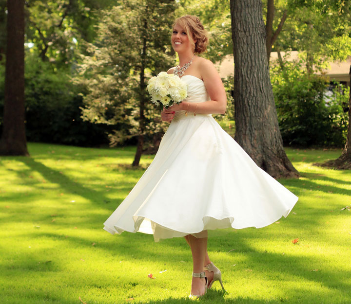 In this Sept. 20, 2014 photo released by Alan D. Charles, Helen Bradley, 27, of DePere, Wis., poses on her wedding day at a country club in Madison, Wis. She chose a short gown for three reasons: comfort, affordability and the chance to show off her accessories.