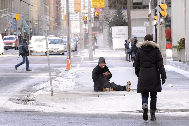 A homeless man sits on a subway ventilation shaft in downtown Toronto to keep warm from the extreme cold temperature of near the minus 20 degrees Celsius mark, Toronto, Ont., January 7, 2014.