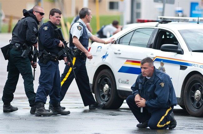 Police keep watch on a house as they search for a heavily armed gunman following the shooting of three Mounties in Moncton, N.B., on June 4, 2014.