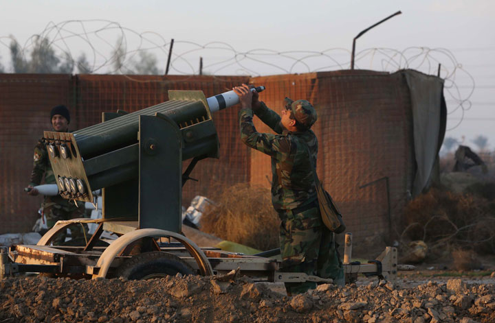 An Iraqi soldier loads a multiple rocket launcher during clashes between Islamic State group fighters and a coalition of combatants made up of the Iraqi army and pro-government fighters including the Al-Abbas Fighting Division on January 2, 2015.
