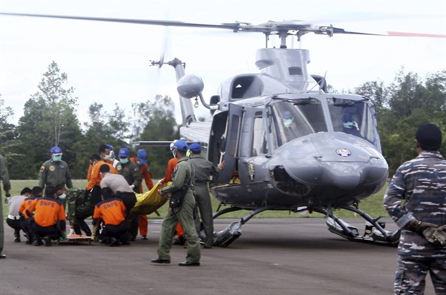 Indonesian military personnel unload the bodies believed to be the victims of AirAsia Flight 8501 from a helicopter at Iskandar Airport in Pangkalan Bun, Central Borneo, Indonesia, Thursday, Jan. 22, 2015.