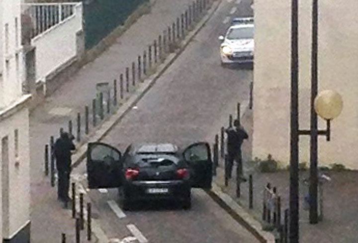 Armed gunmen face police officers near the offices of the French satirical newspaper Charlie Hebdo in Paris on Jan. 7.