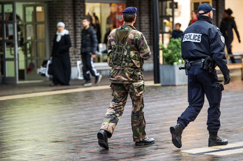 A French police officer and a soldier patrol in a street of Roubaix, northern France, on January 13, 2015.