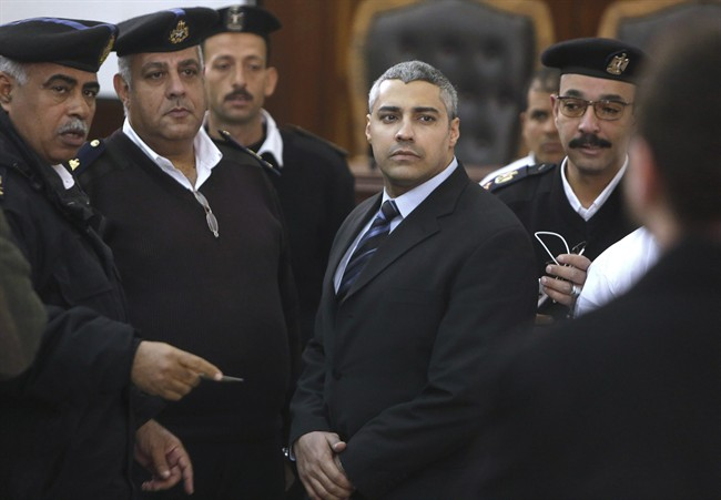Canadian Al Jazeera English journalist Mohamed Fahmy, speaks with policemen during his retrial in Cairo, Egypt, Monday, Feb. 23, 2015. The retrial of two Al-Jazeera English journalists who face terror-related charges in a case widely criticized by human rights organizations and media groups has been postponed to March 8.
