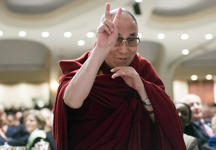 The Dalai Lama gestures a peace symbol as he is introduced during the National Prayer Breakfast in Washington, DC, February 5, 2015.