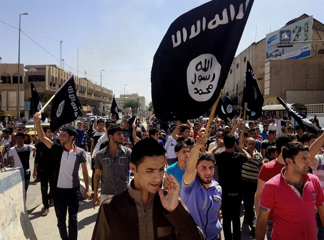 FILE - In this Monday, June 16, 2014 file photo, demonstrators chant pro-Islamic State group slogans as they wave the group's flags in front of the provincial government headquarters in Mosul, 225 miles (360 kilometers) northwest of Baghdad, Iraq.