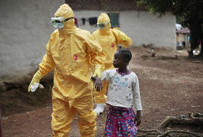 FILE - In this Sept. 30, 2014, file photo, nine-year-old Nowa Paye is taken to an ambulance after showing signs of the Ebola infection in the village of Freeman Reserve, about 30 miles north of Monrovia, Liberia.
