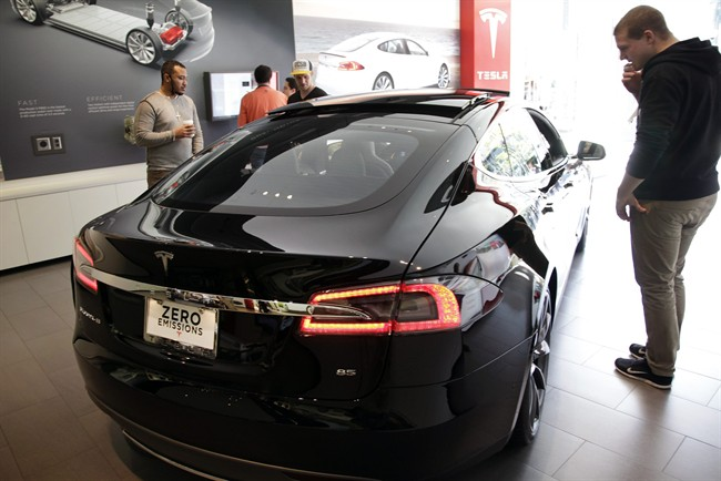 People check out the Tesla model S at the Tesla showroom at the the Third Street Promenade in Santa Monica, Calif.