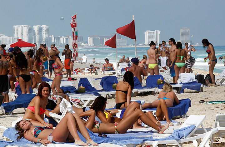 In this March 10, 2012 file photo, people hang out on the beach during spring break in Cancun, Mexico. The beach resort remains a top destination for American spring-breakers seeking an escape from winter.