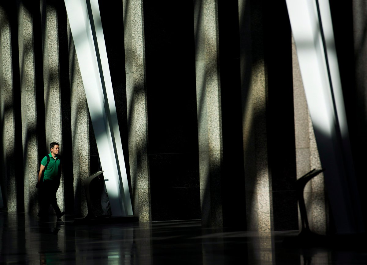 A man makes his way to work though the early morning light at Brookfield Place in downtown Toronto on Wednesday, August 13, 2014.