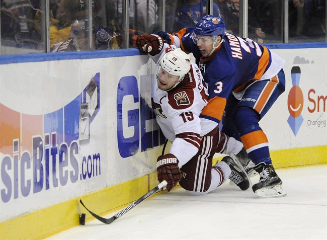 Arizona Coyotes right wing Shane Doan (19) and New York Islanders defenceman Travis Hamonic (3) battle for the puck against the boards in the third period of an NHL hockey game at Nassau Coliseum on Tuesday, Feb. 24, 2015.