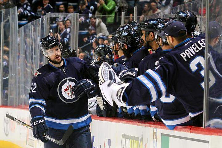 Drew Stafford (12) of the Winnipeg Jets celebrates his first-period goal against the Los Angeles Kings with teammates at the bench on Sunday at the MTS Centre in Winnipeg.