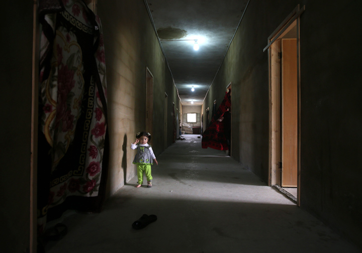 A Syrian girl stands in the corridor of a refugee centre where she lives with her family in northern Lebanon in this image from May, 2014.