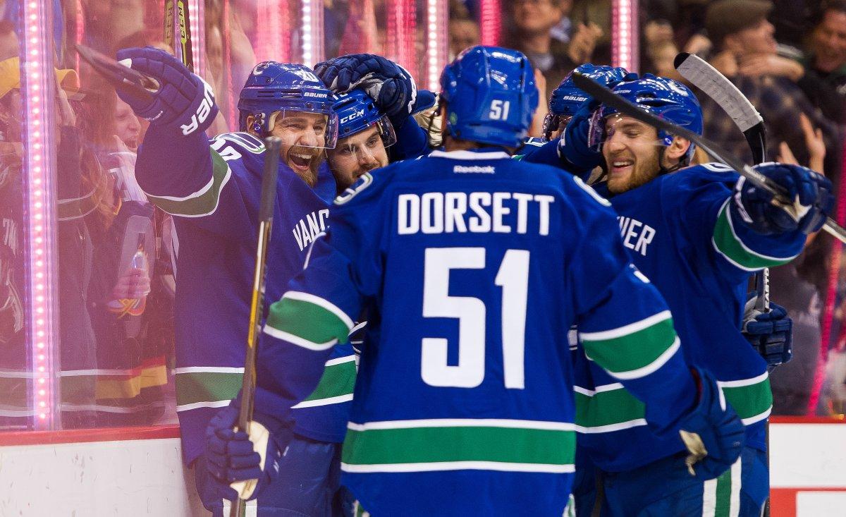 Chris Higgins #20 celebrates with teammates Derek Dorsett #51, Yannick Weber #6 and Brad Richardson #15 after scoring a goal against the Toronto Maple Leafs.