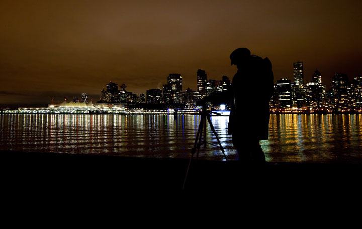 A woman takes photographs after many downtown buildings turned their lights off during Earth Hour in Vancouver, B.C., on Saturday March 31, 2012.