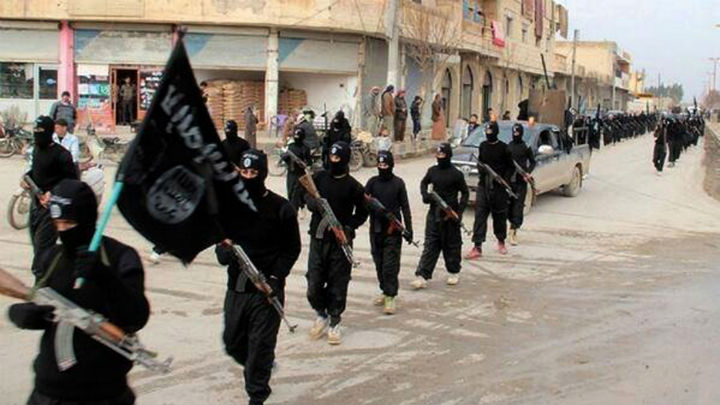 This undated file image posted on a militant website on Tuesday, Jan. 14, 2014 shows ISIS fighters marching in Raqqa, Syria.