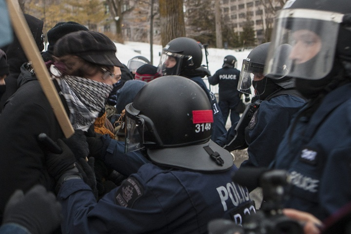 Protesters and police scuffle during a protest against austerity organized by the ASSE student group in Quebec City, Thursday, March 26, 2015.