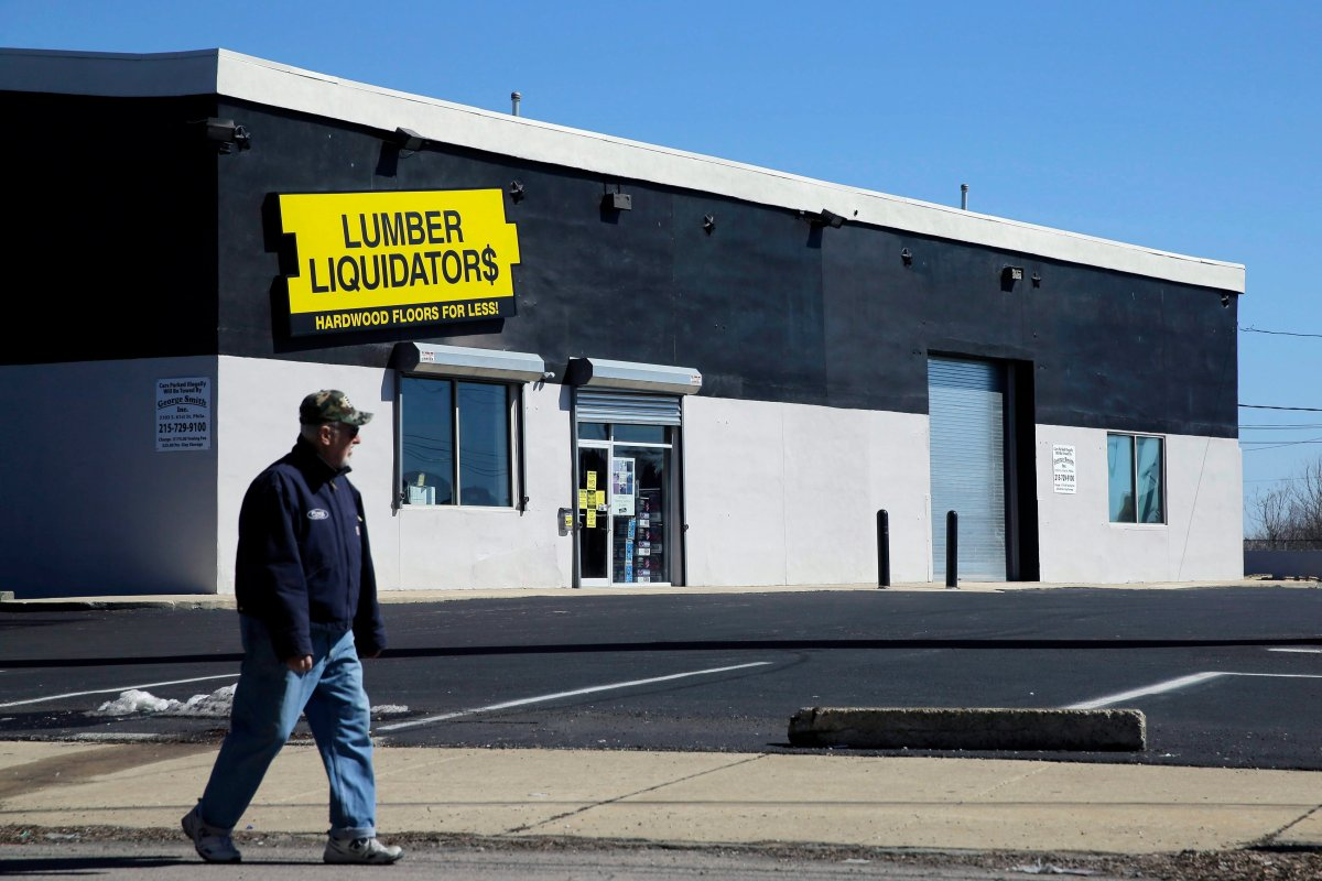 A man walks past a Lumber Liquidators store, Thursday, March 12, 2015, in Philadelphia. The Justice Department is pursuing criminal charges against the retailer.