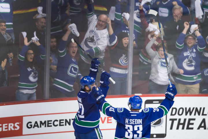 Vancouver Canucks' Daniel Sedin, left, celebrates his goal against the Calgary Flames with his twin brother Henrik Sedin, both of Sweden, during the third period of game 5 of an NHL Western Conference first round playoff hockey series in Vancouver, B.C., on Thursday April 23, 2015.