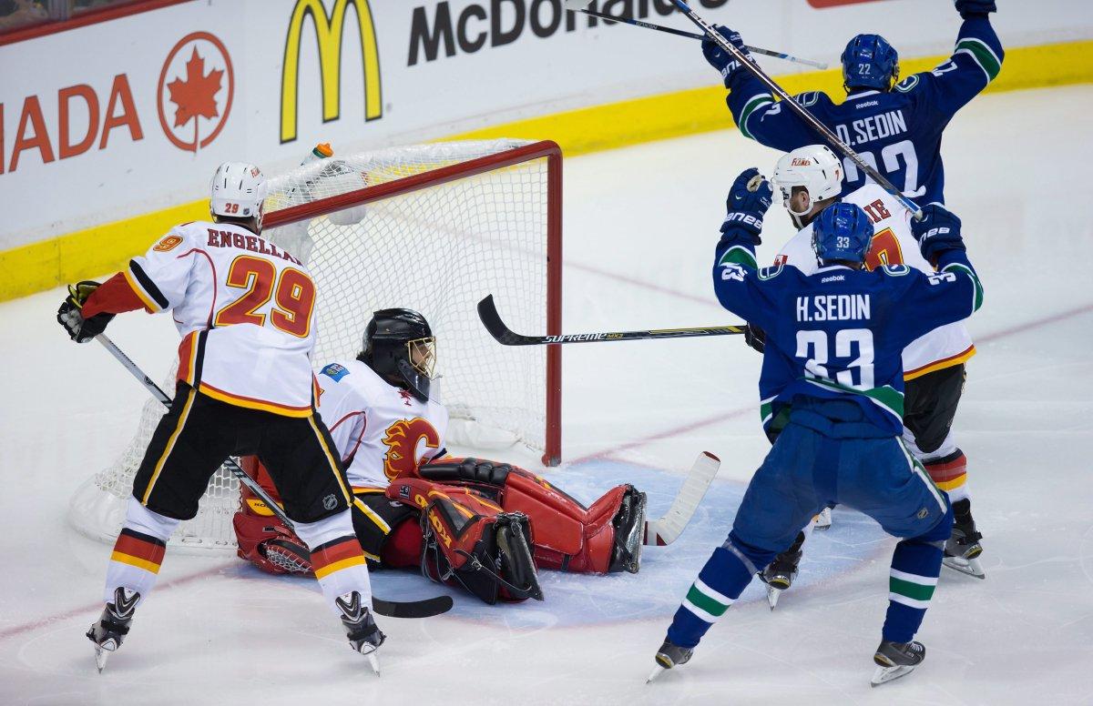 Vancouver Canucks' Daniel Sedin and Henrik Sedin celebrate Daniel's goal against Calgary Flames' goalie Jonas Hiller.