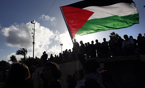 Palestinians wave a giant national flag during a demonstration marking Land Day on March 30, 2015 near the Damascus Gate in Jerusalem's Old City.