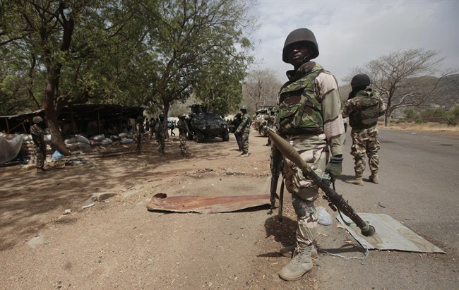 FILE - In this file photo taken Wednesday, April 8, 2015, Nigerian Soldiers man a check point in Gwoza, Nigeria, a town newly liberated from Boko Haram.