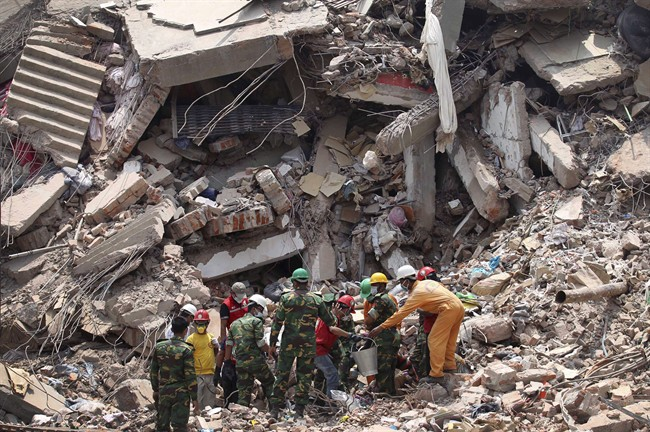 Workers try to release two bodies trapped in the rubble of collapsed Rana Plaza garment factory building in Savar, near Dhaka, Bangladesh, April 30, 2013. (File photo).
