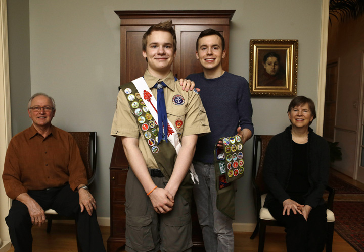 In this file photo, Boy Scout Pascal Tessier, now 18, center left, and his brother Lucien pose for a portrait with their parents,.