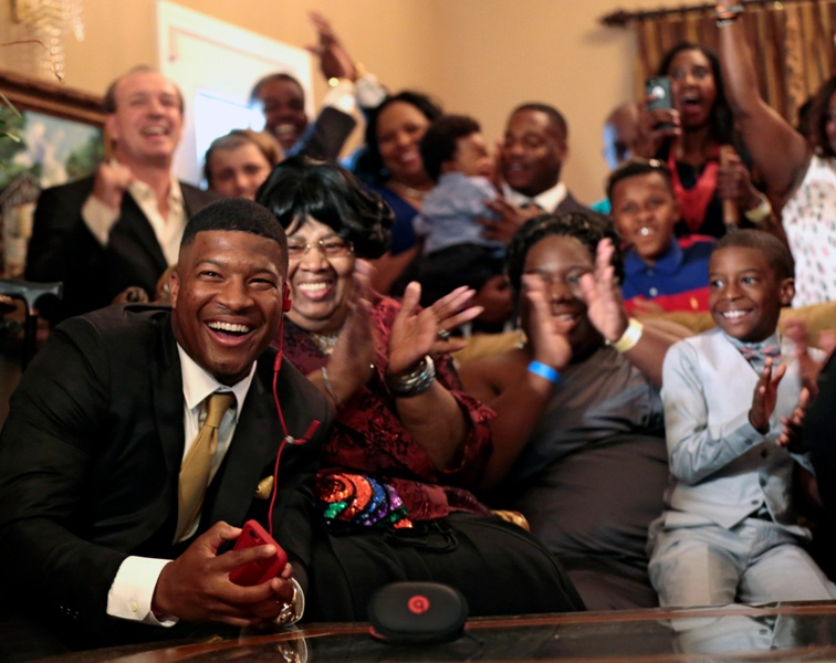 Jameis Winston reacts with his family and friends as he takes the call from the Tampa Bay Buccaneers that they are selecting him as the number one draft pick, Thursday, April 30, 2015, in Bessemer, Ala.