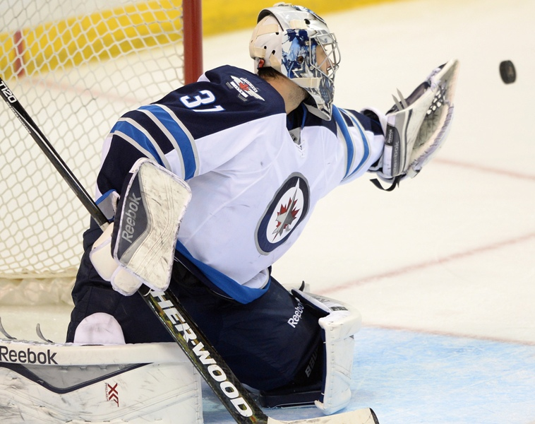 Winnipeg Jets' goalie Ondrej Pavelec (31), of Czech Republic, makes a glove save against the St. Louis Blues during the third period of an NHL hockey game, Tuesday, April 7, 2015, in St. Louis.