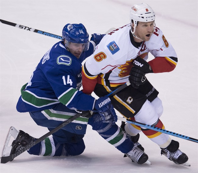 Vancouver Canucks left wing Alex Burrows (14) fights for control of the puck with Calgary Flames defenseman Dennis Wideman (6) during the second period of NHL playoff action in Vancouver, B.C. Wednesday, April 15, 2015. Burrows was taken to hospital Tuesday after suffering an unspecified injury at the team's morning skate.THE CANADIAN PRESS/Jonathan Hayward.