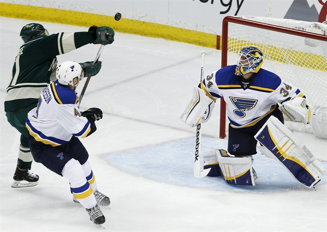 St. Louis Blues goalie Jake Allen (34) deflects a shot back toward Minnesota Wild left wing Zach Parise, left, and Blues defenseman Carl Gunnarsson, center, of Sweden, during the first period of Game 3 of an NHL hockey first-round playoff series game in St. Paul, Minn., Monday, April 20, 2015.