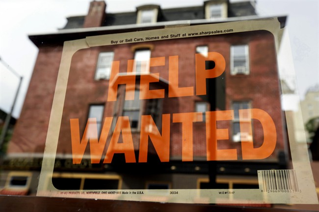 """A a shopper walks past a store with a """"Help Wanted"""" sign in the window."""