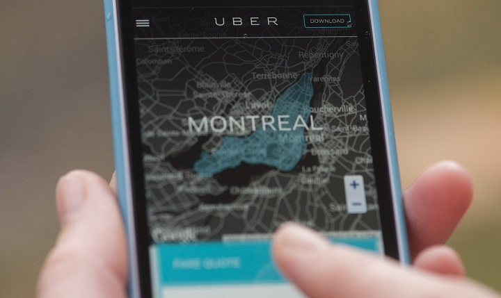A woman browses an Uber website on her smartphone in Montreal, Monday, November 24, 2014.