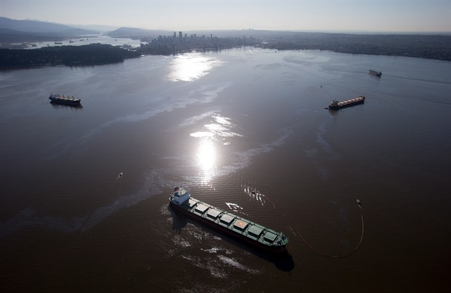 Crews on spill response boats work to contain bunker fuel leaking from the bulk carrier cargo ship Marathassa, second right, on Burrard Inlet in Vancouver, B.C., on Thursday April 9, 2015.