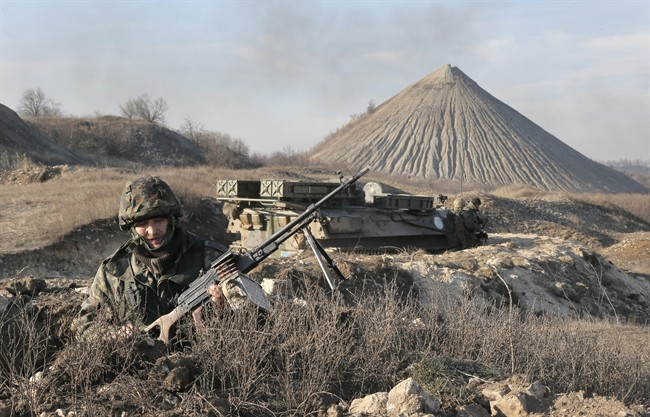 FILE - In this March 11, 2015, file photo, a Ukrainian serviceman takes position at the front line outside Kurahovo, in the Donetsk region of Ukraine.