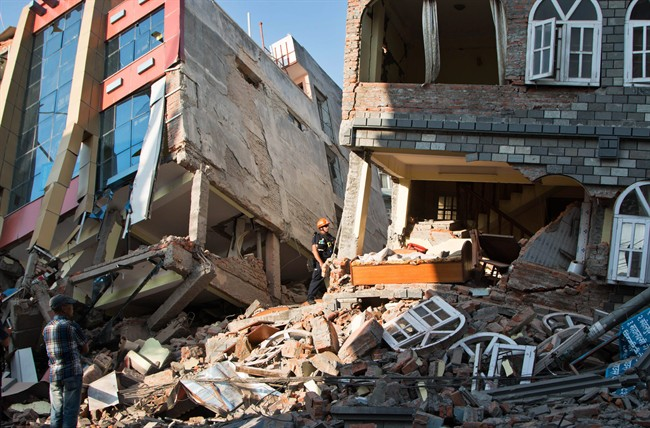 A rescue worker stands beside buildings that collapsed in an earthquake in Kathmandu, Nepal, Tuesday, May 12, 2015.