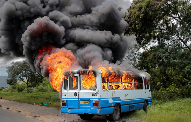 A bus burns after being set on fire by demonstrators in the Ngagara district of Bujumbura, Burundi Tuesday, May 12, 2015. A crowd who were marching to the funeral of a woman who died in recent protests were blocked from doing so by police, and the crowd then set fire to a bus and government car and motorcycle.