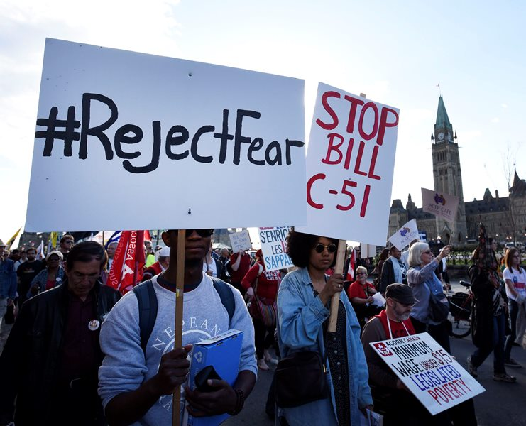 People rally against Bill C-51, the government's anti-terror legislation, as they pass Parliament Hill during a International Workers' Day protest against austerity measures in Ottawa on Friday, May 1, 2015.