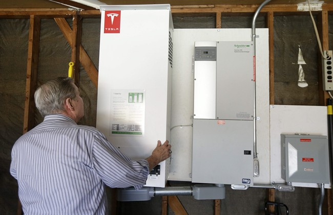 David Cunnigham shows a prototype Tesla battery system that powers his Foster City, Calif. home.