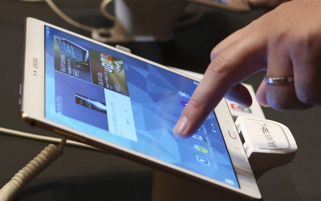 A visitor tries out a Samsung tablet during an event in Tokyo, July 31, 2014.