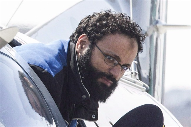 Chiheb Esseghaier, one of two men accused of plotting a terror attack on rail target, is led off a plane by an RCMP officer at Buttonville Airport just north of Toronto on April 23, 2013.