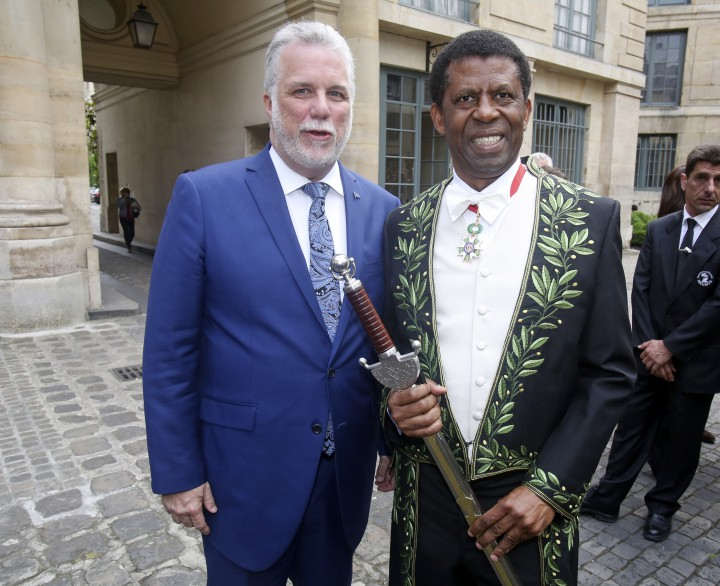 Haitian-born Canadian writer Dany Laferriere poses with Quebec Premier Philippe Couillard, left, after his induction ceremony at the Academie Francaise, French Academy, in Paris, Thursday May 28, 2015.