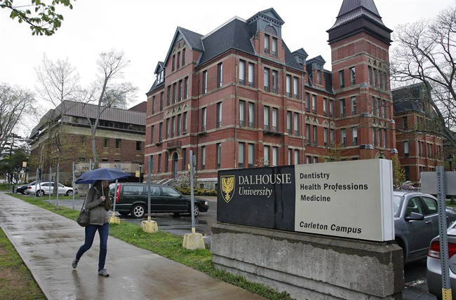 A pedestrian walks by the Dalhousie Dentistry Building in Halifax on Friday, May 22, 2015. A report into sexist online posts by dentistry students at Dalhousie University has found that a Facebook page at the centre of the scandal began as a bonding exercise, but turned offensive. Despite the report's findings, the university says the academic standards class committee determined the men are eligible to graduate as long as they satisfy their clinical requirements.